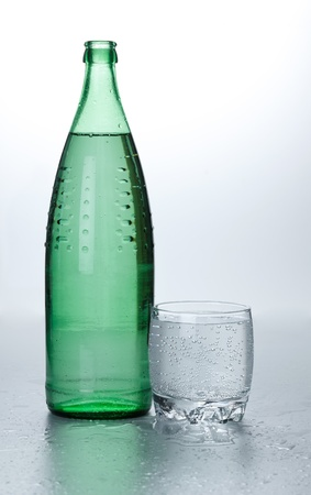 carbondioxide: Glass of water near bottle on wet surface