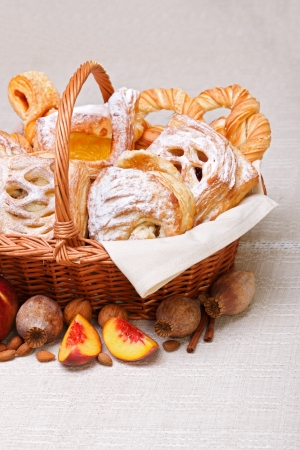 Lots of sweet cakes in basket, fruit and poppy decoration around Stock Photo - 19112031