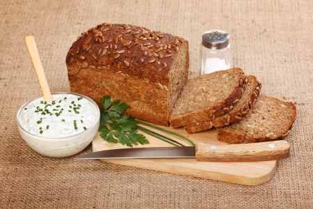 Brown sliced bread with seeds on wooden board, spicy sour cream Stock Photo - 19112039