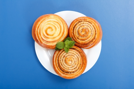 Top view of three cinnamon rolls on white plate, blue background Stock Photo - 19112013