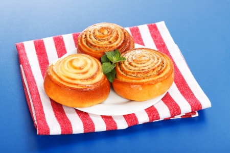 Three cinnamon rolls on white plate, blue background Stock Photo - 19112034