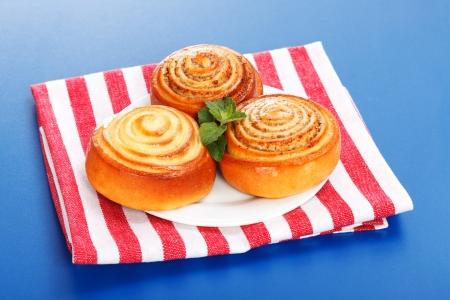Three cinnamon rolls on white plate, blue background Stock Photo - 19112034