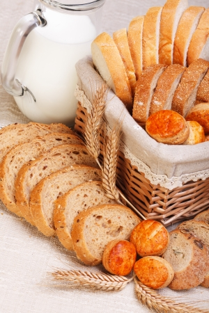 Assorted bakery products sliced, arranged in small basket and around. Wheat ears in front, milk jug behind Stock Photo - 19112045
