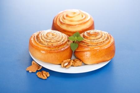 Three cinnamon rolls on white plate, walnut decoration, blue background Stock Photo - 19112012