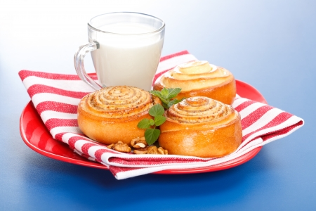 Three cinnamon rolls and jug of milk on red plate, blue background Stock Photo - 19112008