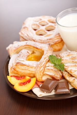 Breakfast: apple, peach, sour cherry cakes and milk on plate, chocolate and peach slices decoration Stock Photo - 19112005