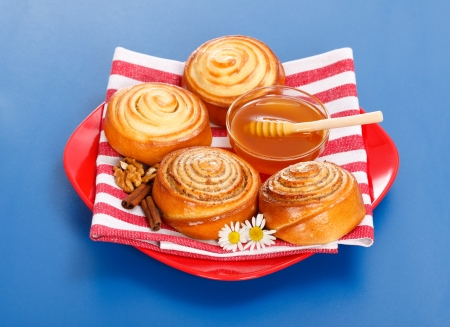 Cinnamon rolls and honey on red plate, blue background Stock Photo - 19112028