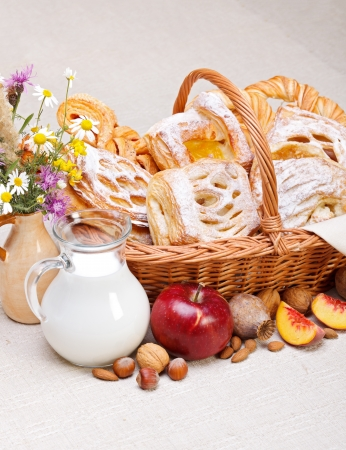 Lots of sweet cakes in basket, fruit and milk decoration around Stock Photo - 19112022