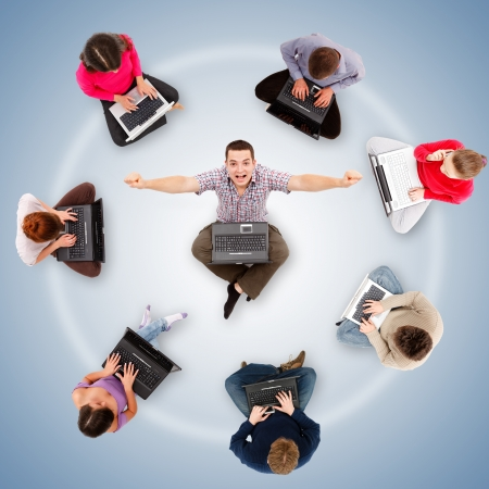 Social network members sitting with their laptop computers around a successful, happy man's circle Stock Photo - 19177791
