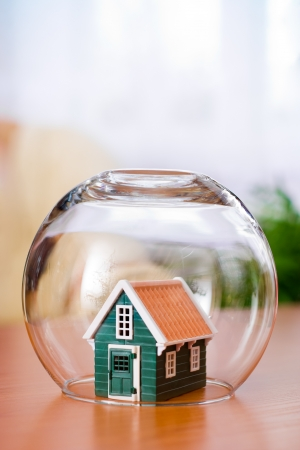 house insurance: House insurance concept: covered with a glass ball to protect