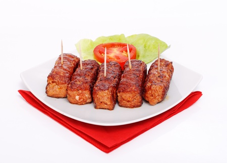 frilled: Traditional romanian food - frilled meat rolls - mititei, mici - served with salad and tomato Stock Photo