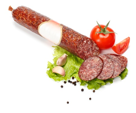 Salami stick with blank label and slices around, vegetables around photo