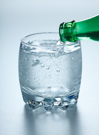 carbondioxide: Mineral water being poured into glass from green bottle