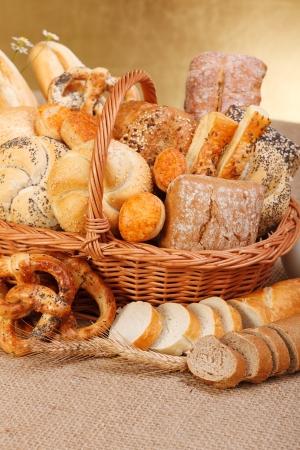 canasta de panes: Composici?n de los diversos productos de panader?a en cesta en el fondo r?stico Foto de archivo