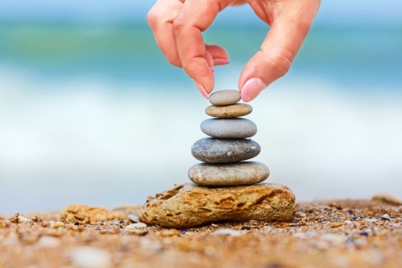 Hand placing the last pebble of a stacked tower on the sea side