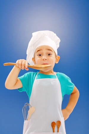 Little chef tasting food from wooden spoon on blue background