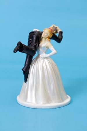 La novia y el novio de la torta en el fondo azul