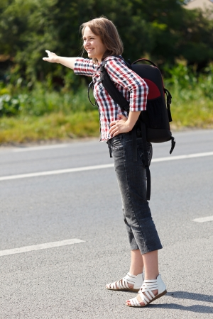 hitch hiker: Teen girl hitch hiking on the road Stock Photo