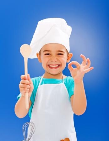 niños cocinando: Pequeño cocinero alegre que muestra el buen gusto y la cuchara de madera Foto de archivo