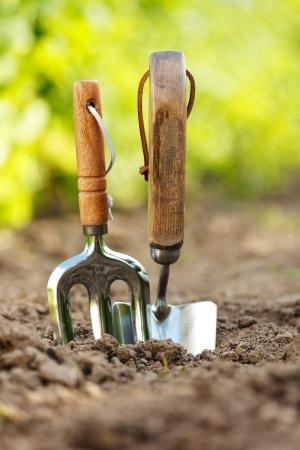 Garden tools stuck in soil in garden