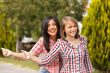 hitch hiker: Teen girls hitch hiking in town Stock Photo