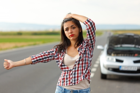 hitch hiker: Sad woman hitch-hiking on the road in front of her broken car Stock Photo