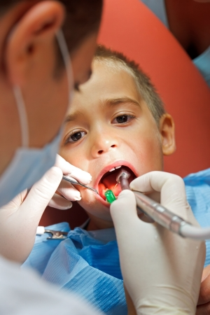 Little boy sitting at dentist, his teeth being drilled photo