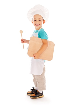 Happy little boy as chef with wooden board and spoon