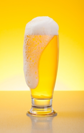 overflow: Glass full of tasty overflowing pale lager beer on yellow background