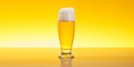 pilsner beer: Alcoholic beverage in glass over yellow background Stock Photo