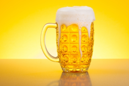 pilsner beer glass: Pale lager beer overflowing in glass on yellow background