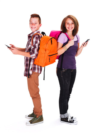 Happy teenage students with tablet and telephone in hand photo