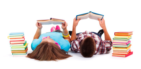 Teens with books next to them laying on the floor and reading Banque d'images