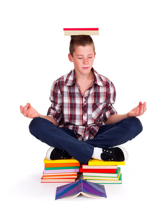 Teenage schoolboy sitting on books, meditating in lotus position Stock Photo