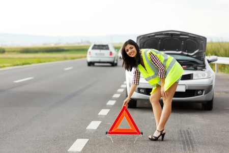 Woman in reflective vest placing emergency triangle in front of her broken car