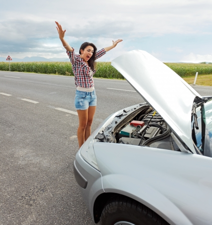 frustrate: Mad woman shouting in anger because of her cars failed engine Stock Photo