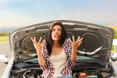 broke: Woman being very angry because of her cars failed engine Stock Photo