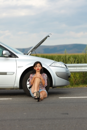 Angry woman sitting near her broken car photo