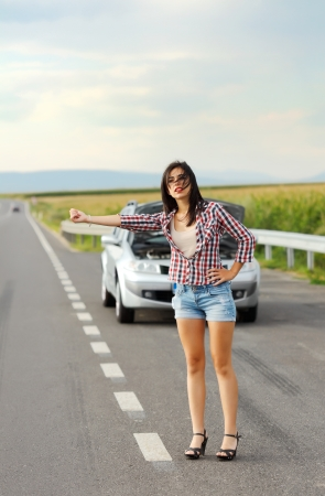 car trouble: Sad woman hitch-hiking in front of her car with failed engine Stock Photo