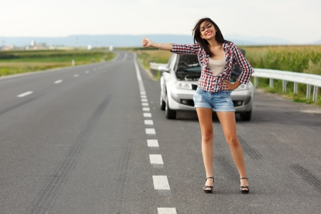 Woman driver kindly hitch-hiking on the road in the front of her broken car photo