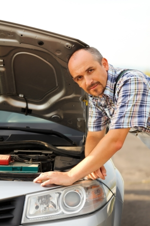 Repairman near a car with failed engine photo