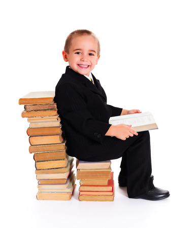kindly: Cute little boy with open book sitting and smiling kindly