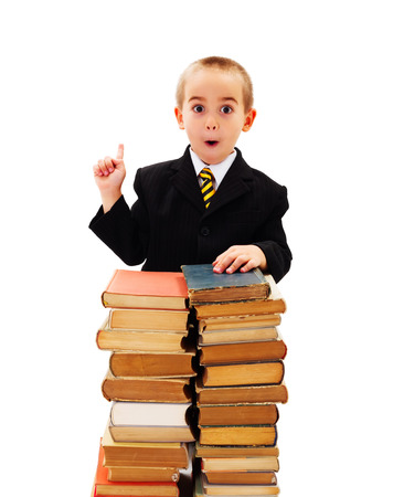 Surprised boy pointing upward to copy space, stack of old books in front photo