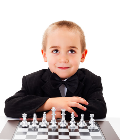 chess player: Cute little kid waiting for a playmate for a chess round Stock Photo