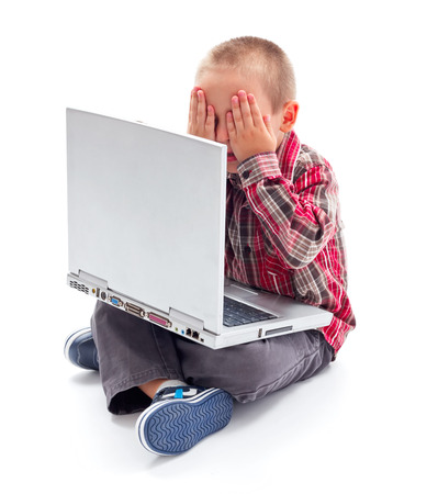 Kid sitting in front of laptop with his hand hiding her face