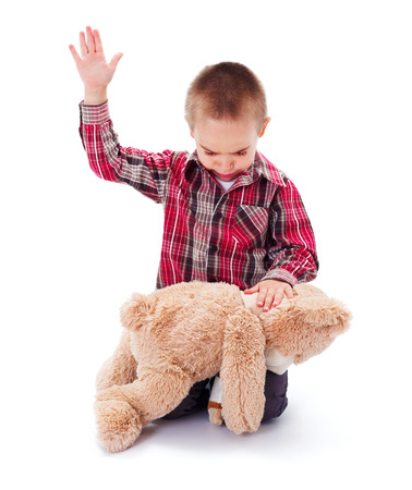 Angry little kid beating his teddy bear - domestic abuse concept