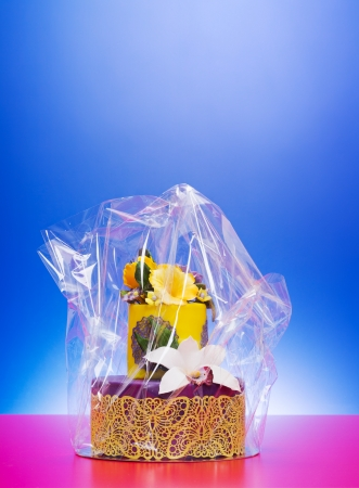 cellophane: Colorful purple-yellow cake decorated with edible candy flowers and lace in cellophane wrap Stock Photo