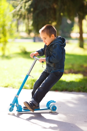 Playful boy riding a kick scooter in a park photo