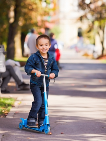 Joyful little boy with kick scooter playing outdoors photo