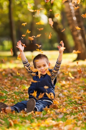 play ground: Playful kid playing with autumn leaves in a park Stock Photo